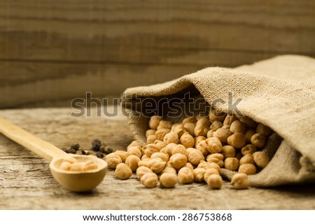 scattered chickpeas from a jute bag with a spoon on old wooden background - stock photo