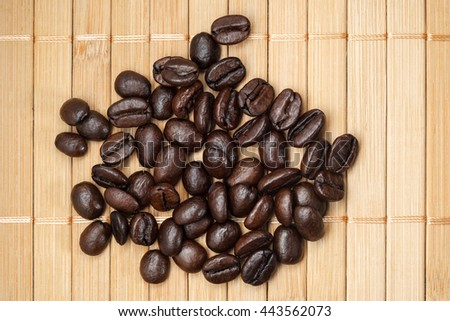 Scattered coffee grains on a bamboo napkin, closeup