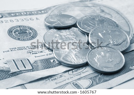 Scattered coins atop a ten dollar US bill, in monochrome with blue toning. - stock photo