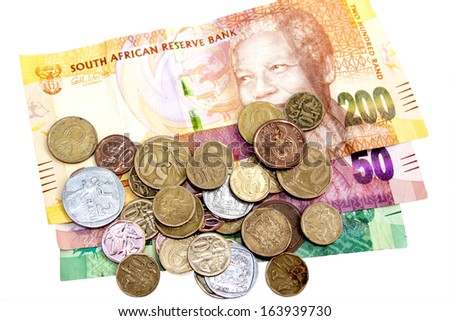 scattered coins on three South African Rand bank notes - stock photo