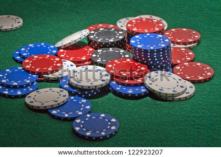 Scattered colorful poker chips on the green table