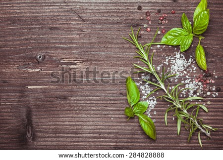 Scattered fresh basil and rosemary, sea salt and dry peppercorns with copy space - stock photo