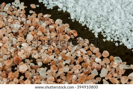 Scattered Himalayan pink salt crystals vs white salt crystals on rusty metal background - stock photo