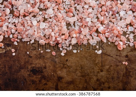 Scattered Himalayan pink salt, top view on rusty metal background space for text - stock photo