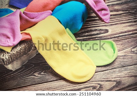scattered multi-colored socks and laundry basket on a wooden background. toned photo - stock photo