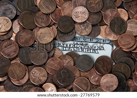Scattered pennies on top of a hundred dollar bill.
