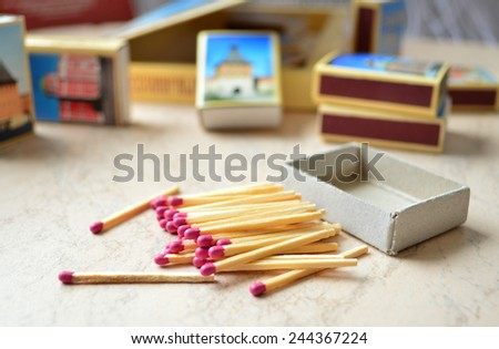 Scattered pink-head matches and a set of souvenir match-boxes. - stock photo