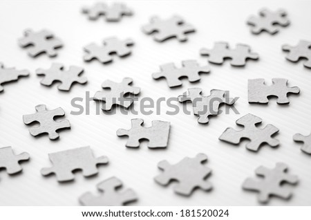 Scattered puzzle pieces toy isolated on white background. Concept photo of disharmony, change, no-order and chaos. (BW) - stock photo