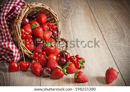 Scattered ripe summer berries from basket - stock photo