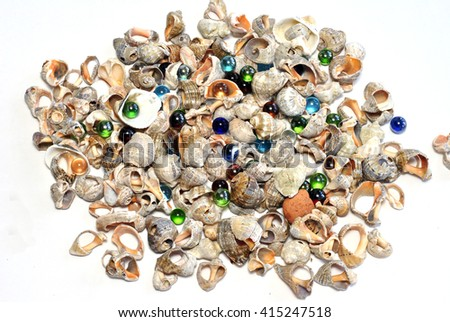 Scattered seashells and colored glass beads - stock photo