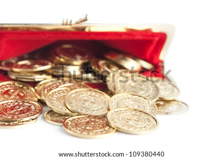 Scattered silver and gold coins are in open red purse, isolated on white background. A great number of coins symbolize wealth, richness, income and profit. Close up shot. - stock photo