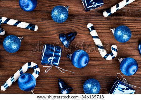 Scattered variety of Christmas toys on fir tree on a wooden background - stock photo