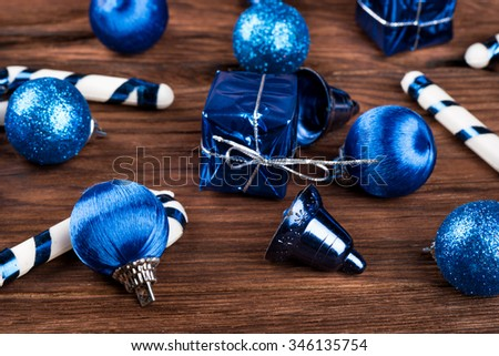 Scattered variety of Christmas toys on fir tree on a wooden background closeup - stock photo