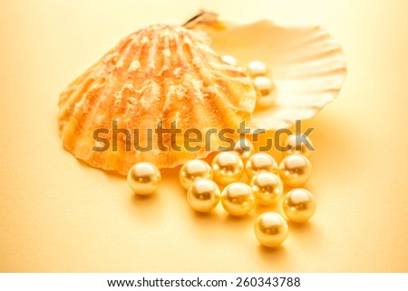 Scattering white pearls with seashell in toning - stock photo