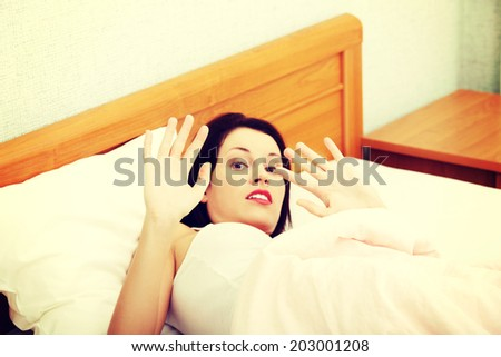 Sceared woman is lying in bed and protect by hands, in home. Violence concept. - stock photo