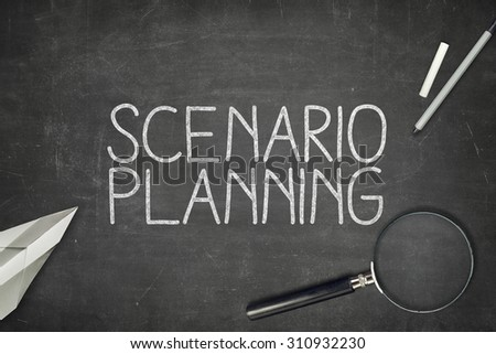 Scenario planning concept on blackboard with magnifying glass - stock photo
