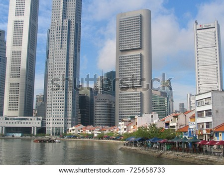 Scene along the singapore river with village in foreground and modern skyscrapers in background year