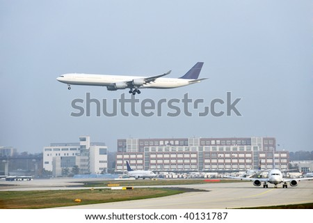 scene at the airport - an airplane waiting for start and an aircraft taking off - stock photo