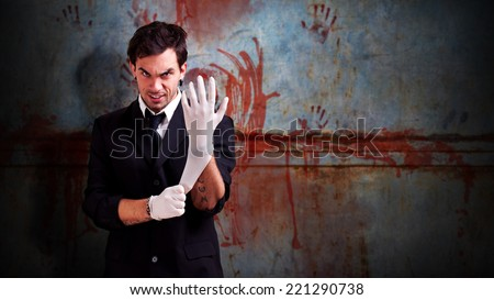 scene like in a horror movie with a man, looking psychotic, putting on a latex glove and standing in front of a wall with bloody fingerprints - stock photo