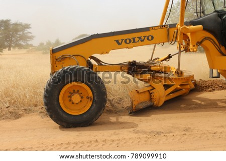 Scene of a grader used to level a dirt road in North of Senegal in Louga region. The long yellow machine is pushing the soil to trace the road. The picture has been taken on 13rd november 2015.