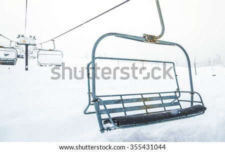 scene of close up  ski lift with seats going over the snow mountain  in ski resort. - stock photo