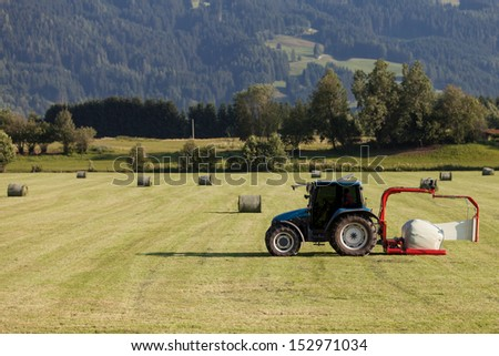 Scene of haymaking, tractor with hay cart working on the field  as agricultural background. Harvesting - stock photo