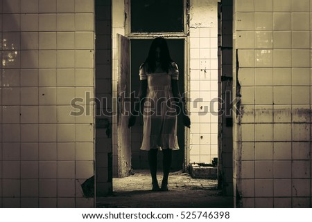 Scene of macabre and horror of scary woman staying in white dress in demolished hallway