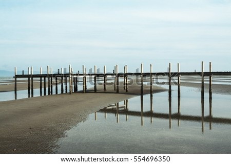 Scene of Turquoise water sea at low tide at Cambodia seacoast. Wooden pier.