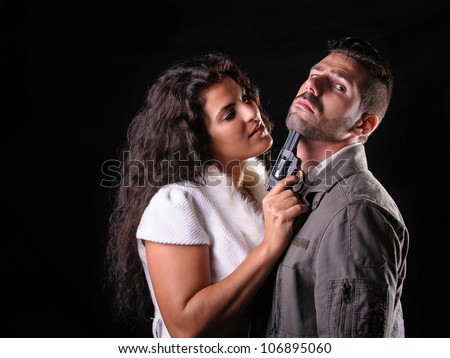 scene of violence with a firearm between a  man and a woman - stock photo