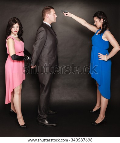 Scene of violence with firearm between men and women. Elegant lady holding gun aiming at man in suit on black and grey background in studio. - stock photo