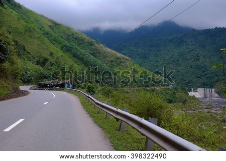 Scene on Ho Chi Minh trail on clouds day, house on hill, danger terrain with mountain pass, people cross stream, life on highland Vietnam among green forest