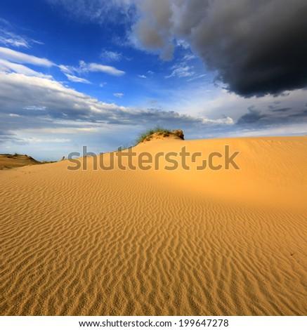 Scene with dunes in sandy desert before thunder storm - stock photo