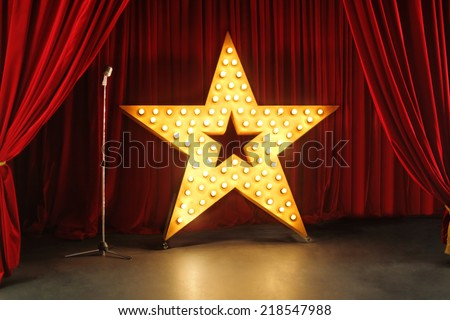 Scene with red curtains and big star with lights - stock photo