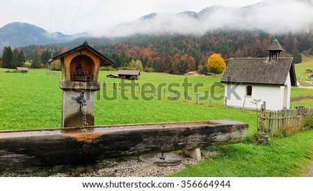 Scenery of a Bavarian farmland with a wooden trough, country houses & barns in a ranch on a foggy autumn morning by the hillside of colorful foliage near Garmisch Partenkirchen and Mittenwald, Germany - stock photo