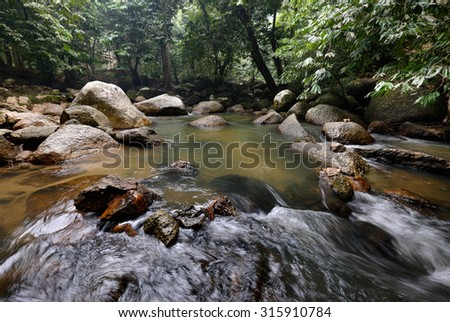 Scenery of a cascaded river flowing through green rain forest in hazy atmosphere.