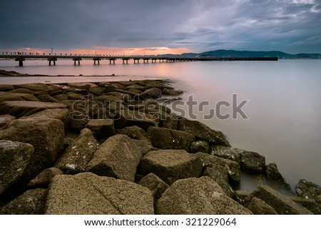Scenery of a fishermen jetty with colorful cloudy background. - stock photo