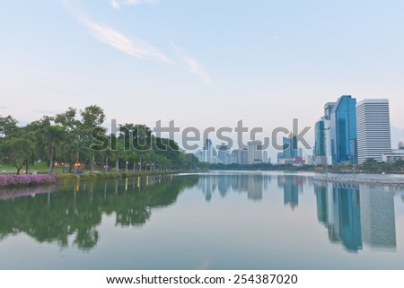 Scenery of a park and Bangkok cityscape view in the evening - stock photo