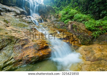 Scenery of a waterfall in green rainforest and streaming water with motion blur in the foreground