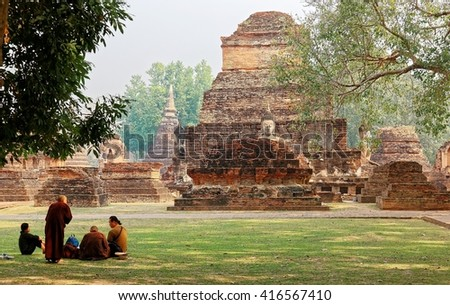 Scenery of ancient Buddha statues among ruined Stupas in Temple Wat Mahathat & people sitting on meadows before the ruins in Sukhothai Historical Park, a beautiful UNESCO heritage site in Thailand  - stock photo