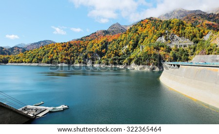 Scenery of autumn lake with boats parking by lakeside and mountains of colorful foliage by Kurobe Dam in Tateyama Kurobe Alpine Route, Japan - stock photo