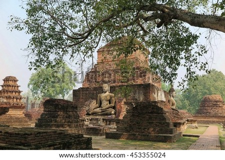 Scenery of giant ancient Buddha statues in meditation posture among ruins of an ancient Buddhist Temple, Wat Mahathat in Sukhothai Historical Park, a beautiful UNESCO heritage site in Thailand - stock photo