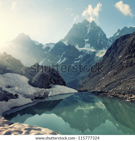 scenery of high mountain with lake and high peak - stock photo