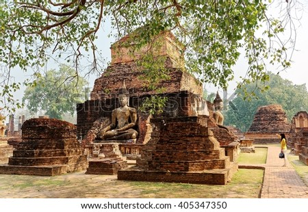Scenery of huge ancient Buddha statues among ruins of Temple Wat Mahathat in Sukhothai Historical Park, a beautiful UNESCO heritage site in Thailand ~ A Tourist taking selfies before the ruined towers - stock photo
