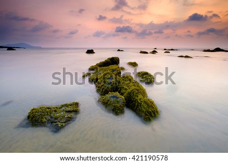 Scenery of Kemasik beach in Terengganu, Malaysia during low tide with colorful cloudy sky in the background and mossy rocks in the foreground. Soft focus due to long exposure. - stock photo