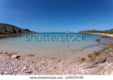 Scenery of lonely island beach with blue sky and turquoise sea on the Adriatic Sea island of Dugi Otok near Kornati, Croatia - stock photo