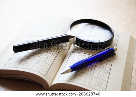 Scenery of Puzzle book, magnifying glass and pen on table - stock photo