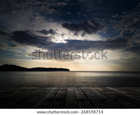 Scenery of the wooden pier with dramatic sky above the sea - stock photo