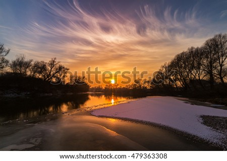 Scenery of wild river with sunset sky reflection, in winter