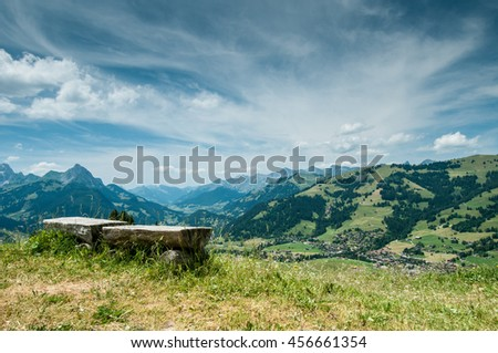 Scenery sunny alpine panorama in Switzerland with view on mountains, green forest, meadow, blue sky and white clouds and with a bench for rest in the foreground - stock photo