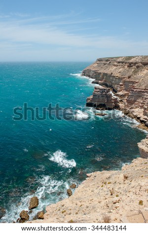 Scenic Aerial panorama of  rugged rock cliff coast formation of Kalbarri National Park in Western Australia, wild sea of Indian Ocean, blue sky, horizon, copy space. - stock photo